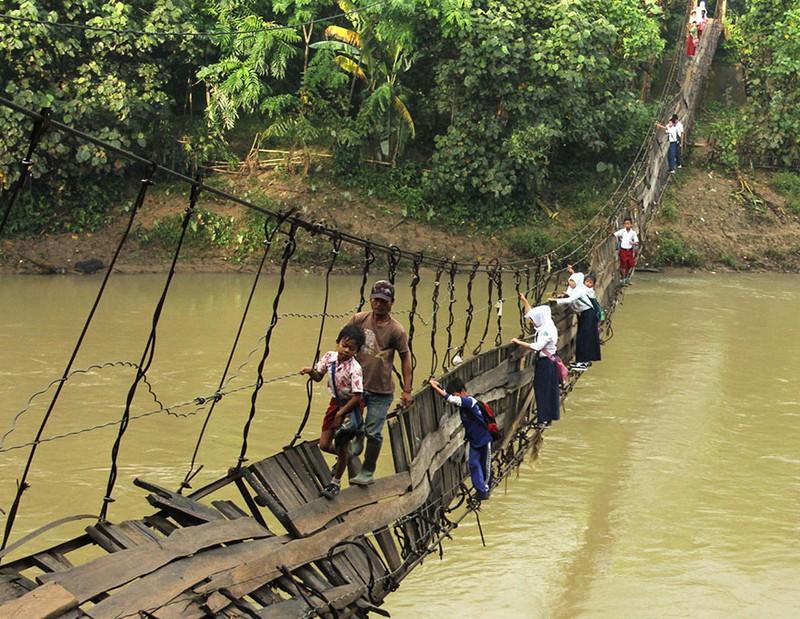 Alumnos cruzando un puente colgante dañado, Lebak, Indonesia. Image credits: Reuters.