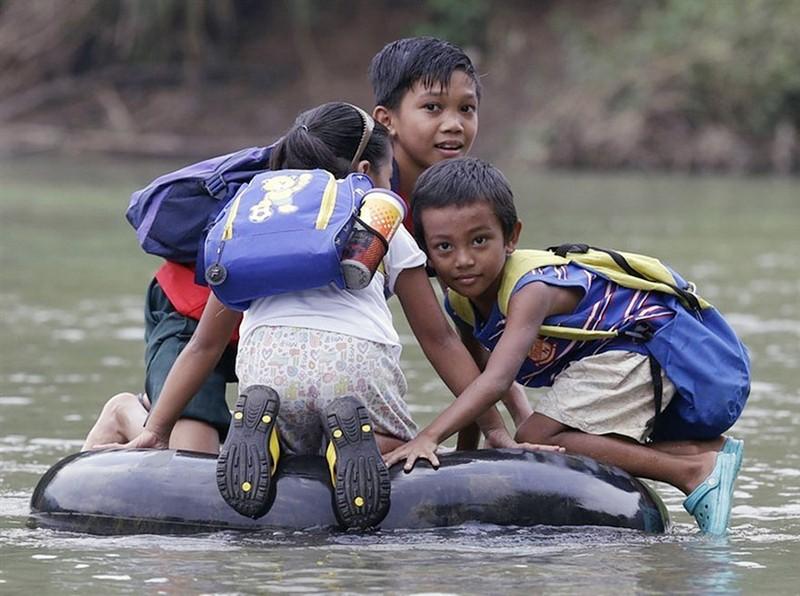 Estudiantes de escuela elemental cruzan un rio en cámaras de automovil hinchadas, Rizal Province, Philippines. Image credits: Bullit Marquez /AP.
